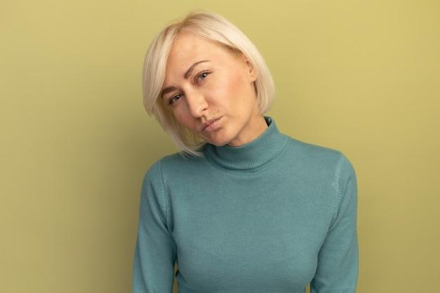 Zuversichtlich hübsche blonde slawische frau, die kamera auf olivgrün betrachtet