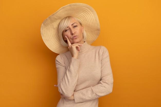 Zuversichtlich hübsche blonde slawische frau mit strandhut legt hand auf kinn auf orange