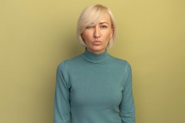 Zuversichtlich hübsche blonde slawische frau schaut kamera auf olivgrün