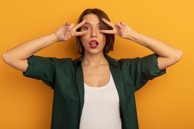 Zuversichtlich hübsche frau steckt zunge heraus und gestikuliert siegeshandzeichen mit zwei händen, die auf orange wand lokalisiert werden