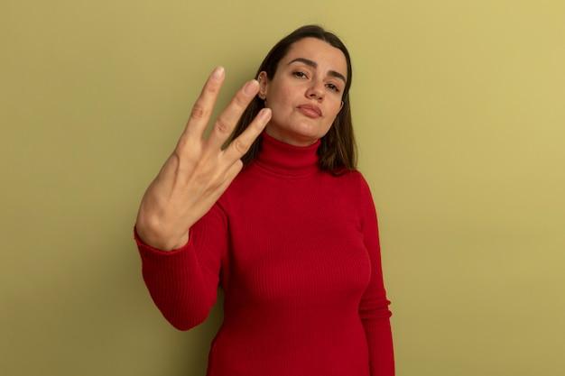 Zuversichtlich hübsche kaukasische frau gestikuliert drei mit den fingern isoliert