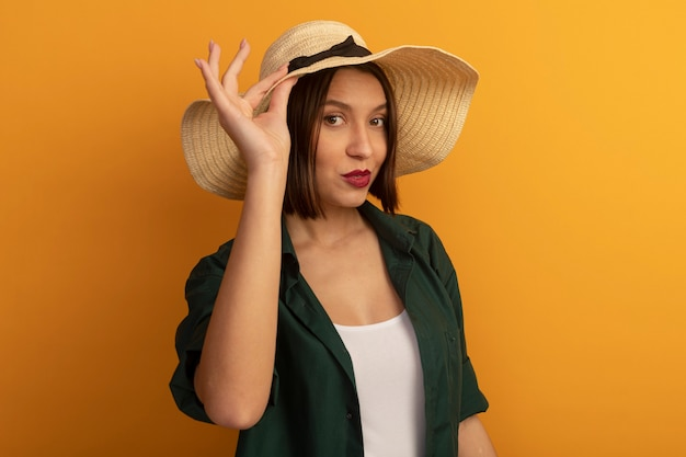 Zuversichtlich hübsche kaukasische frau mit strandhut setzt hand auf hut auf orange
