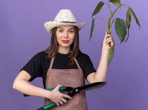 Zuversichtlich hübscher kaukasischer weiblicher gärtner, der gartenhut hält, der gartenschere und pflanzenzweig auf purpur hält