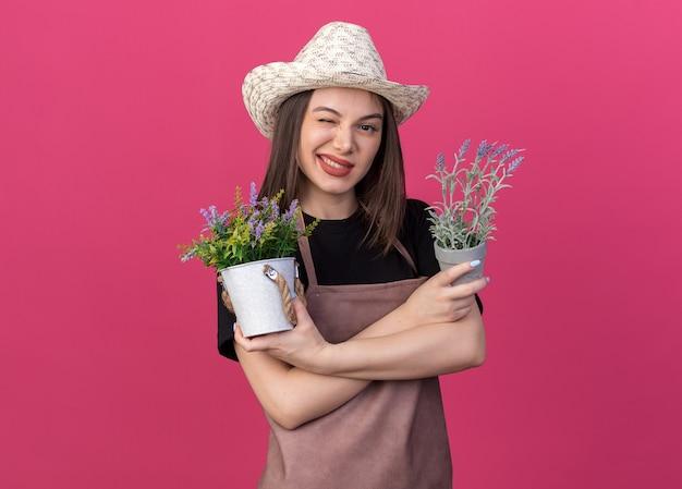 Zuversichtlich hübscher kaukasischer weiblicher gärtner, der gartenhut trägt, blinzelt auge und steht mit verschränkten armen, die blumentöpfe auf rosa halten