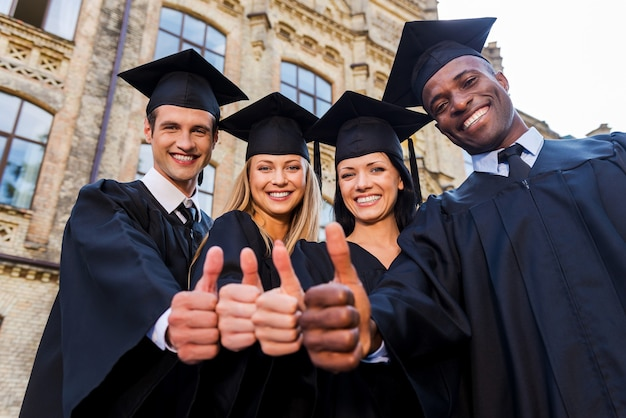 Zuversichtlich in ihre erfolgreiche zukunft. niedrigwinkelansicht von vier hochschulabsolventen in abschlusskleidern, die nahe beieinander stehen und ihre daumen nach oben zeigen