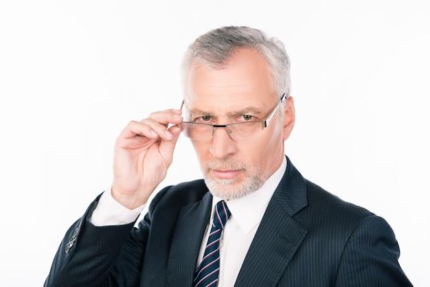 Zuversichtlich intelligenter alter mann im geschäftsanzug, der brille hält