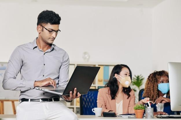 Zuversichtlich intelligenter softwareentwickler, der sich auf einen bürotisch stützt und am laptop arbeitet