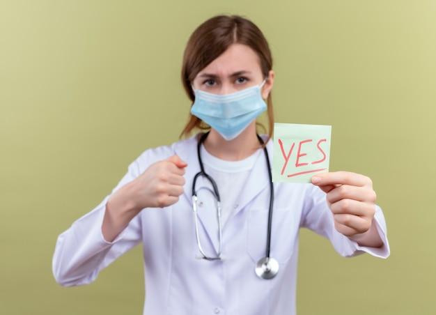 Zuversichtlich junge ärztin, die medizinische robe, maske und stethoskop trägt, die ja anmerkung mit geballter faust auf isolierten grünflächen strecken