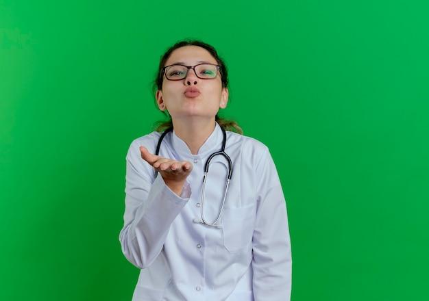 Zuversichtlich junge ärztin, die medizinische robe und stethoskop und brille trägt, die schlagkuss senden, der hand in der luft lokalisiert auf grüner wand mit kopienraum hält