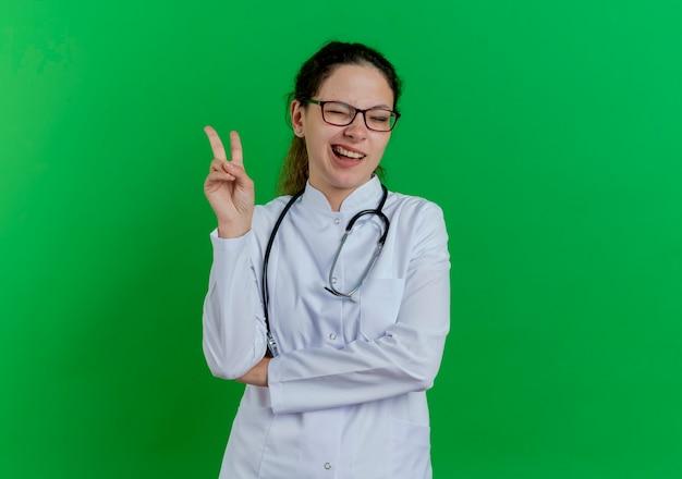 Zuversichtlich junge ärztin, die medizinische robe und stethoskop und brille trägt friedenszeichen zwinkert lokalisiert auf grüner wand mit kopienraum