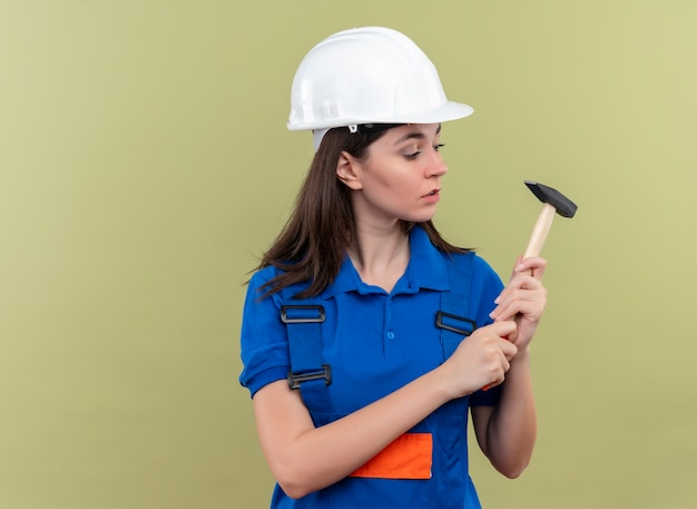 Zuversichtlich junge baumeisterin mit weißem schutzhelm und blauer uniform hält hammer und betrachtet hammer auf lokalisiertem grünem hintergrund mit kopienraum