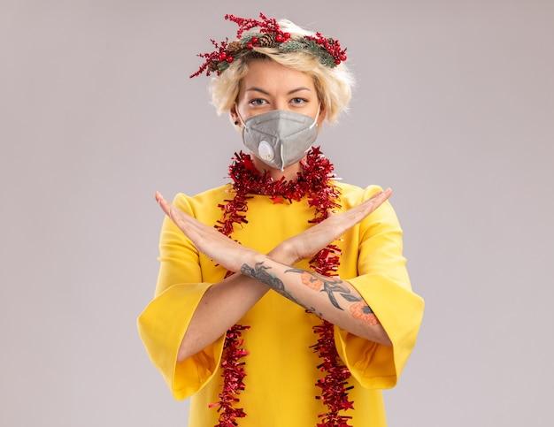Zuversichtlich junge blonde frau, die weihnachtskopfkranz und lametta-girlande um den hals mit schutzmaske trägt, die kamera betrachtet, die keine geste lokalisiert auf weißem hintergrund mit kopienraum tut