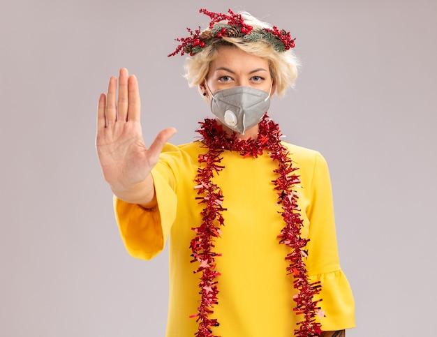 Zuversichtlich junge blonde frau, die weihnachtskopfkranz und lametta-girlande um hals mit schutzmaske trägt, die kamera betrachten stoppgeste lokalisiert auf weißem hintergrund