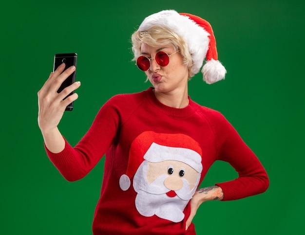 Zuversichtlich junge blonde frau, die weihnachtsmütze und weihnachtsmann-weihnachtspullover mit brille trägt, die hand auf taille hält, die selfie mit gespitzten lippen lokalisiert auf grünem hintergrund nimmt