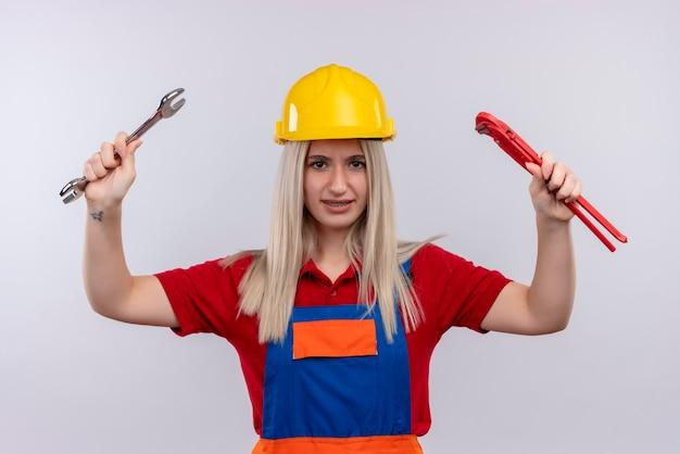 Zuversichtlich junge blonde ingenieur baumeister mädchen in uniform in zahnspangen halten offenen schlüssel und rohrschlüssel auf isolierten weißen raum