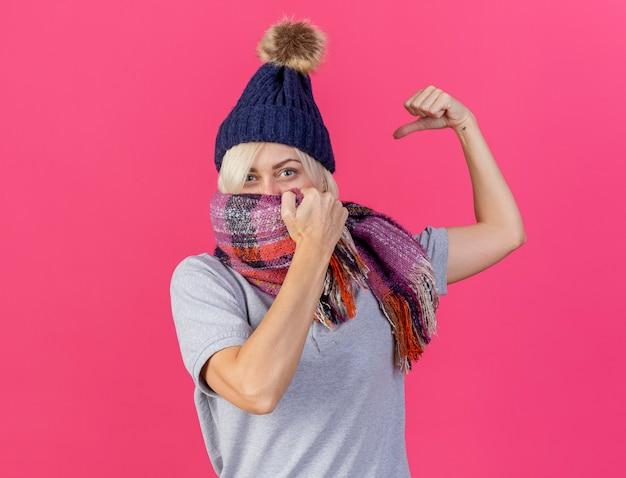 Zuversichtlich junge blonde kranke slawische frau, die wintermütze trägt und schal spannt bizeps lokalisiert auf rosa wand mit kopienraum
