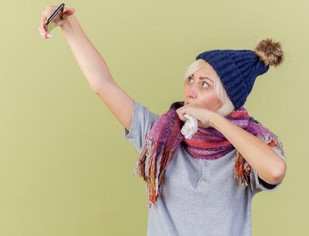 Zuversichtlich junge blonde kranke slawische frau, die wintermütze und schal trägt, hält gewebe, das telefon lokalisiert auf olivgrüner wand mit kopienraum betrachtet