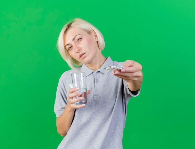 Zuversichtlich junge blonde kranke slawische frau hält glas wasser und packung medizinische pillen isoliert auf grüner wand mit kopierraum
