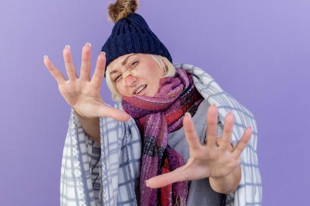 Zuversichtlich junge blonde kranke slawische frau mit medizinischem pflaster auf nase, die wintermütze und schal trägt