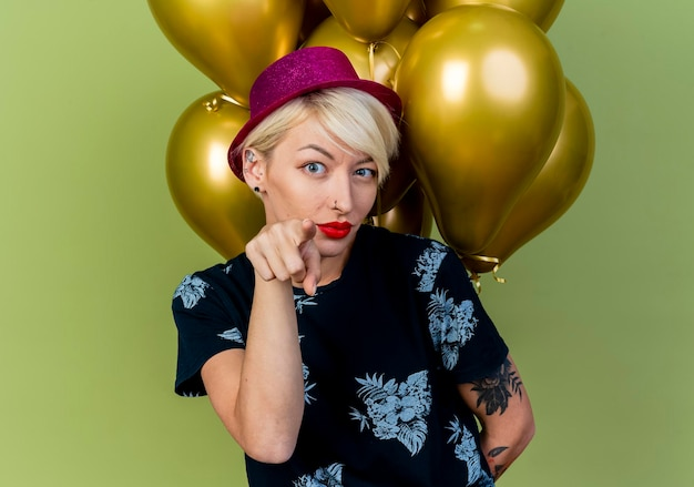 Zuversichtlich junge blonde partyfrau, die partyhut hält, der ballons hinter ihrem rücken hält und nach vorne zeigt, lokalisiert auf olivgrüner wand
