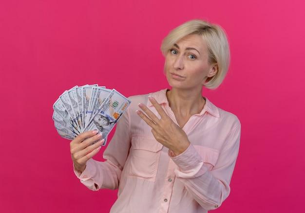 Zuversichtlich junge blonde slawische frau, die geld hält und drei mit hand lokalisiert auf rosa hintergrund zeigt
