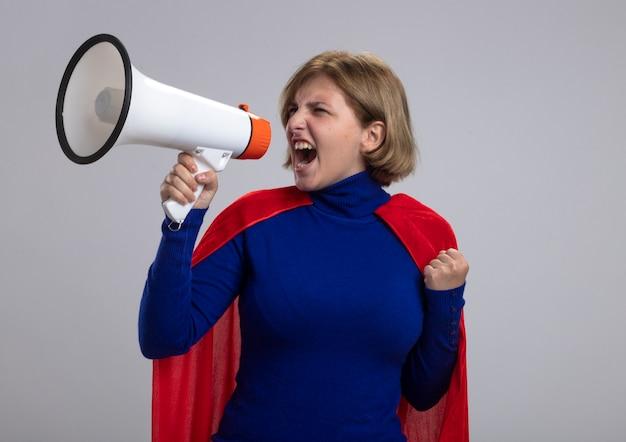 Zuversichtlich junge blonde superfrau im roten umhang, der in der geballten faust des lautsprechers schreit, der seite betrachtet, die auf weißer wand lokalisiert wird