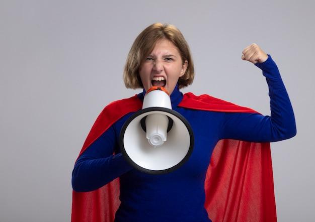 Zuversichtlich junge blonde superfrau im roten umhang, der nach vorne schaut, macht starke geste, die im lautsprecher schreit, der auf weißer wand lokalisiert wird