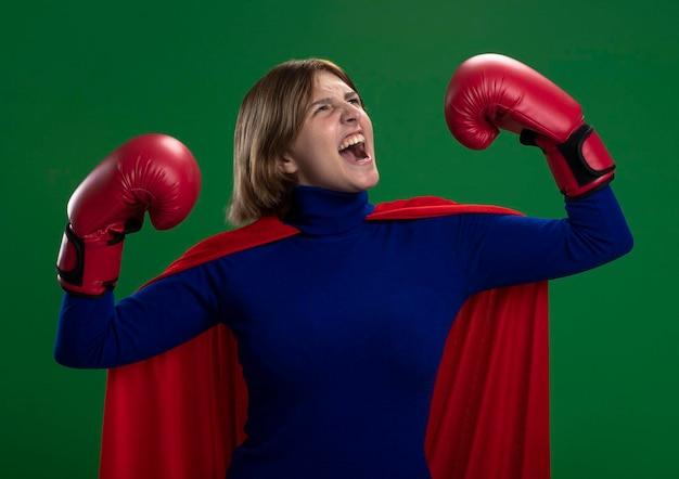 Zuversichtlich junge blonde superheldenfrau im roten umhang, der kastenhandschuhe tut, die starke geste tun, die schreit und lokal auf grüner wand schaut