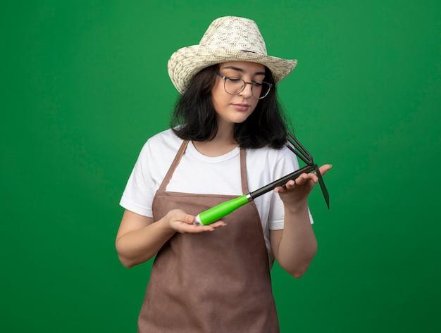 Zuversichtlich junge brünette gärtnerin in optischen gläsern und uniform mit gartenhut hält und betrachtet hacke rechen isoliert auf grüner wand