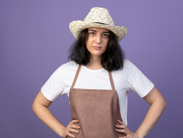Zuversichtlich junge brünette gärtnerin in uniform mit gartenhut legt hände auf taille und schaut nach vorne isoliert auf lila wand