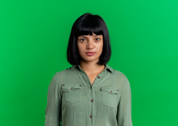 Zuversichtlich junge brünette kaukasische mädchen betrachtet kamera lokalisiert auf grünem hintergrund mit kopienraum
