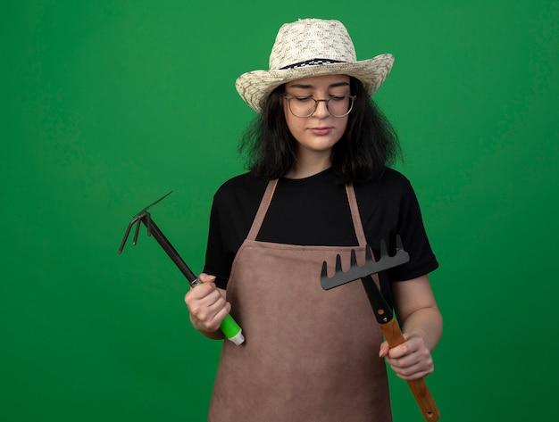 Zuversichtlich junge brünette weibliche gärtnerin in optischen gläsern und uniform, die gartenhut hält, der hacke rechen und rechen lokalisiert auf grüner wand hält