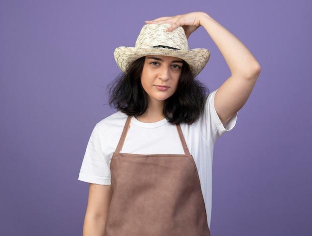 Zuversichtlich junge brünette weibliche gärtnerin in uniform, die hand auf gartenhut trägt und auf lila wand lokalisiert trägt