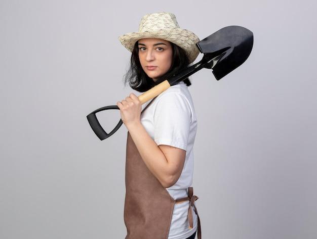 Zuversichtlich junge brünette weibliche gärtnerin in uniform mit gartenhut steht seitlich und hält spaten auf weiß