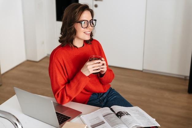 Zuversichtlich junge frau, die am küchentisch zu hause sitzt, mit laptop-computer und arbeitsbuch studiert, tee trinkend