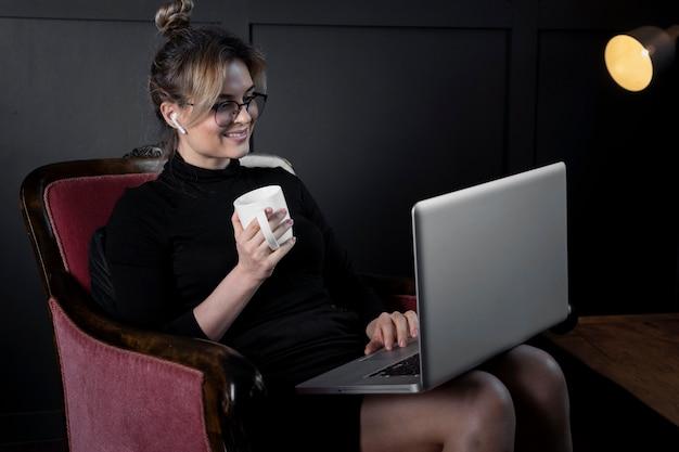 Zuversichtlich junge frau, die an ihrem laptop im büro arbeitet