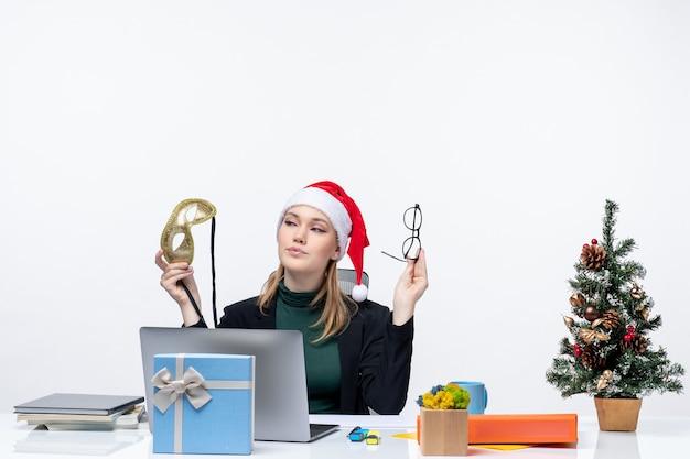 Zuversichtlich junge frau mit santa claus hut brillen und maske sitzen an einem tisch mit einem weihnachtsbaum und einem geschenk darauf im büro auf weißem hintergrund
