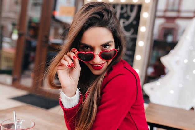 Zuversichtlich junge frau mit schönen braunen haaren, die durch lustige brille zur kamera schauen