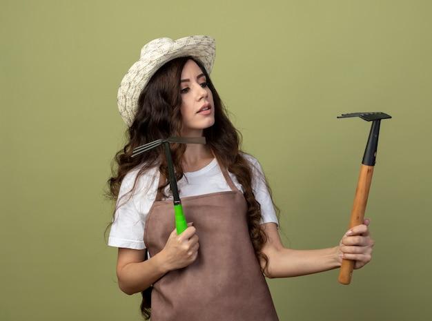Zuversichtlich junge gärtnerin in uniform mit gartenhut hält hacke rechen und betrachtet rechen isoliert auf olivgrüner wand