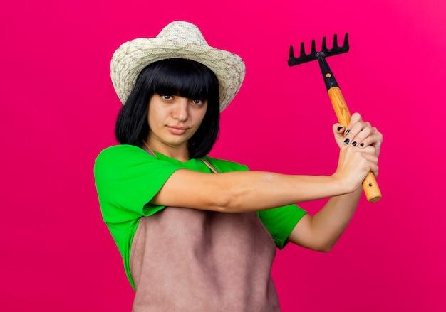 Zuversichtlich junge gärtnerin in uniform mit gartenhut hält rechen mit zwei händen