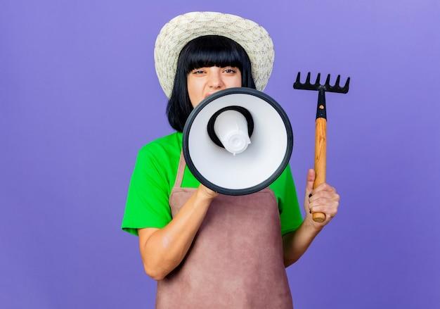 Zuversichtlich junge gärtnerin in uniform mit gartenhut hält rechen und schreit in lautsprecher