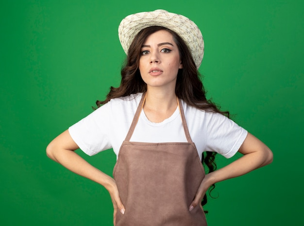 Zuversichtlich junge gärtnerin in uniform mit gartenhut setzt hände auf taille isoliert auf grüner wand mit kopierraum