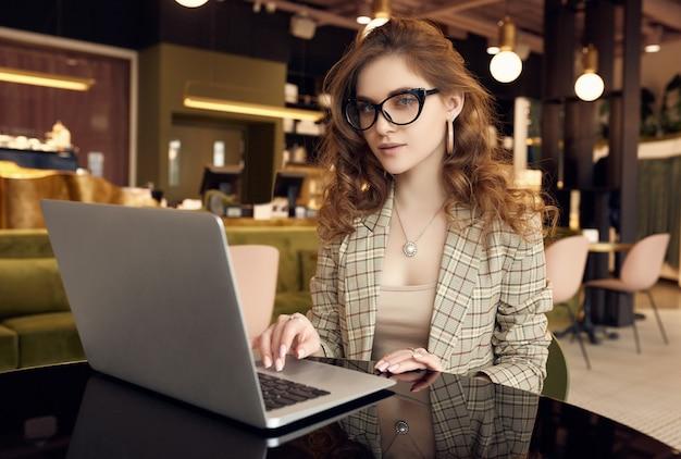 Zuversichtlich junge geschäftsfrau in der intelligenten freizeitkleidung, die am laptop arbeitet