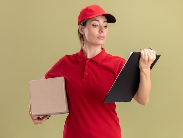 Zuversichtlich junge hübsche lieferfrau in uniform, die cardbox hält und klemmbrett lokalisiert auf olivgrüner wand betrachtet