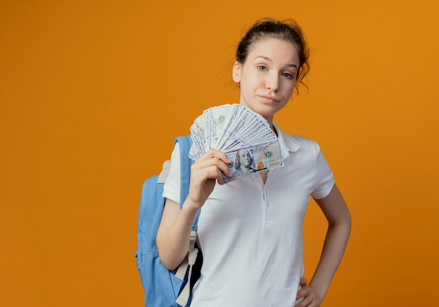 Zuversichtlich junge hübsche studentin, die rückentasche hält geld hält hand auf taille lokalisiert auf orange hintergrund mit kopienraum