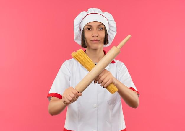 Zuversichtlich junge köchin in der kochuniform gestikuliert nein mit spaghetti-nudeln und nudelholz isoliert auf rosa mit kopienraum