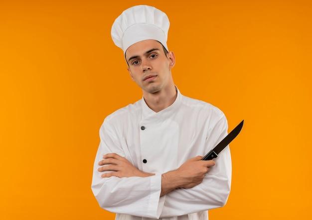 Zuversichtlich junge männliche coole tragende kochuniform, die messer seine hände kreuzt auf isolierter gelber wand mit kopienraum kreuzt