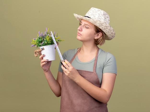 Zuversichtlich junge slawische gärtnerin, die gartenhut misst blumentopf mit maßband auf olivgrün