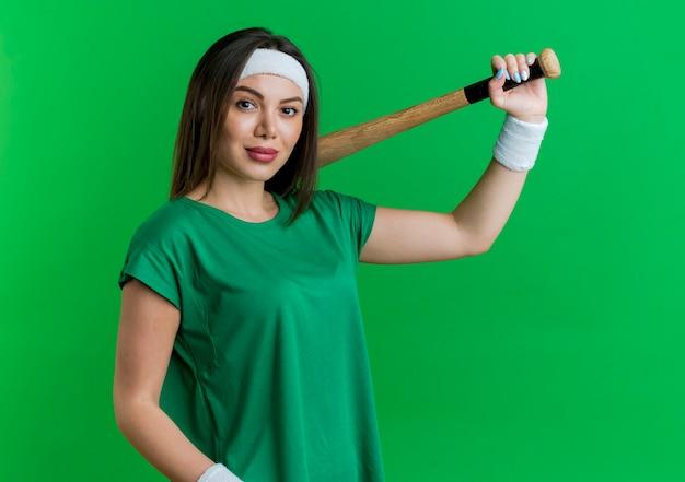 Zuversichtlich junge sportliche frau, die stirnband und armbänder hält baseballschläger suchen
