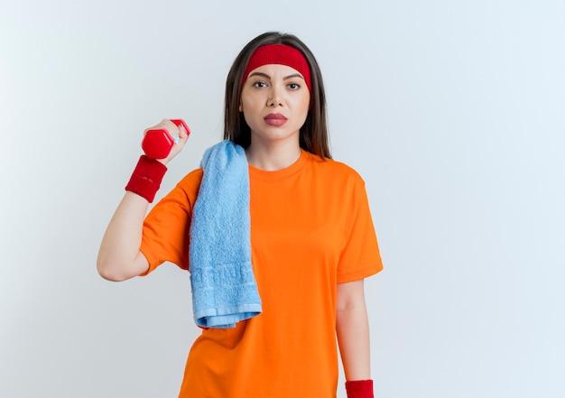 Zuversichtlich junge sportliche frau, die stirnband und armbänder hält hantel mit handtuch auf schulter lokalisiert auf weißer wand mit kopienraum
